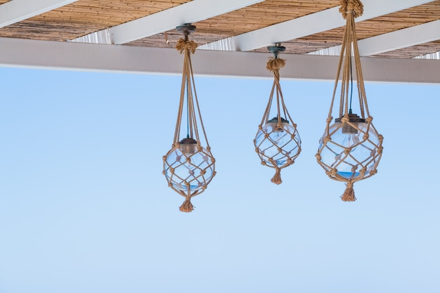 Straw cover the roof of a seaside terrace with hanging lantern.
