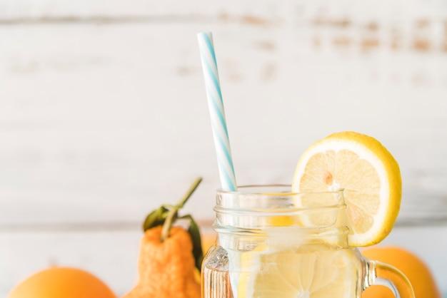 Straw in glass jar garnished with lemon slice