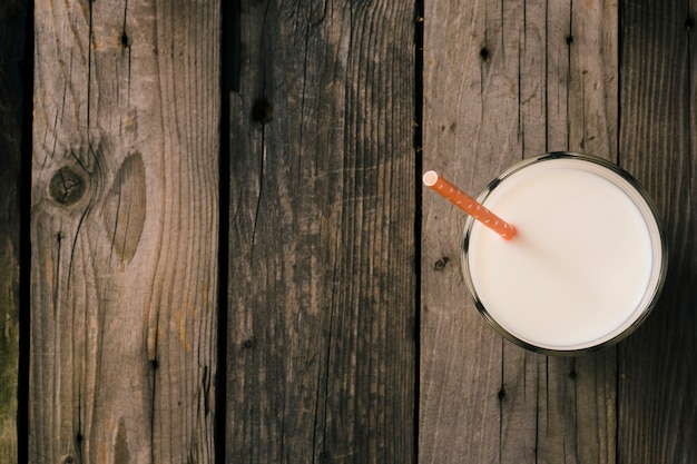 Straw in the glass of milk over the rustic wooden background