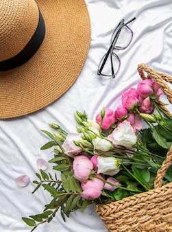 밀짚 모자와 흰색 바탕에 분홍 장미 꽃다발. 상위 뷰, 최소한의 플랫 레이 스타일 구성. 여름 휴가 개념입니다.