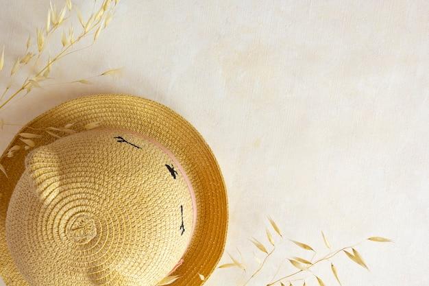 Соломенная шляпа и фото сушеных растений. фотография на бежевом пастельном фоне. копировать пространство