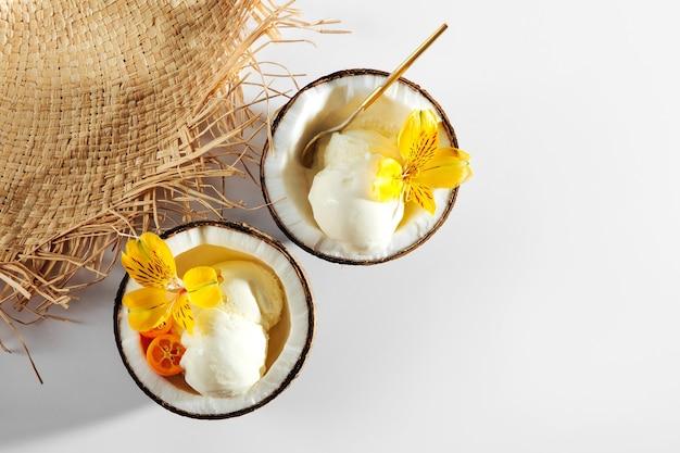 Соломенная шляпа и мороженое в половинке кокоса. концепция летних каникул.