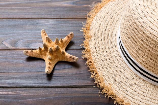 暗い木製の背景に麦わら帽子とヒトデ。コピースペースと上面図の夏休みのコンセプト。