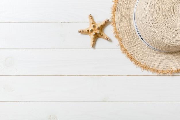 白い木製の背景に麦わら帽子とヒトデ。コピースペースと上面図の夏休みのコンセプト。