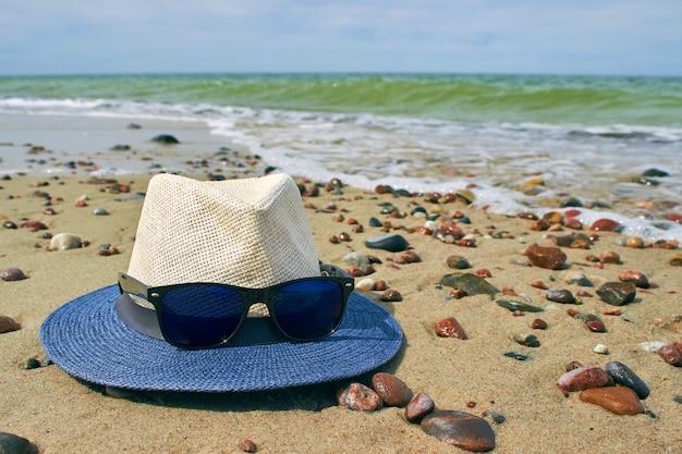Соломенная шляпа и солнечные очки лежат на песчаном берегу моря с галькой.