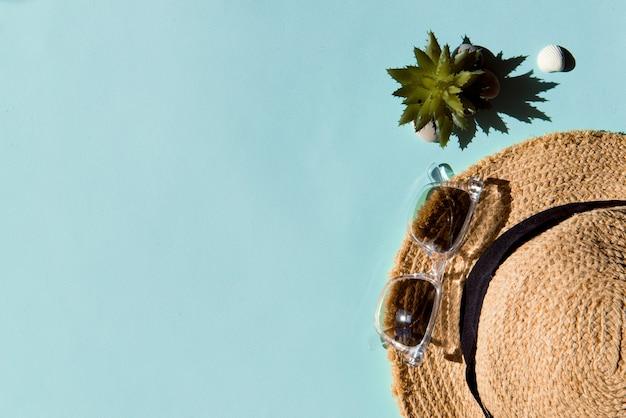 青い色の背景に麦わら帽子とサングラス夏休みフラットレイコピースペース