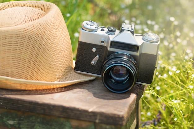 여름 정원에 있는 나무 의자에 있는 밀짚 모자와 빈티지 카메라