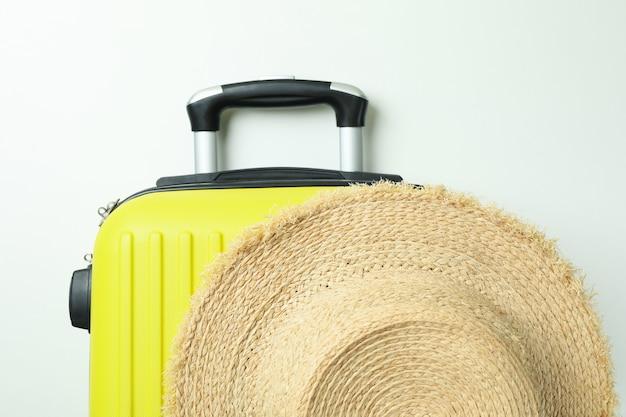 흰색 바탕에 밀 짚 모자와 여행 가방