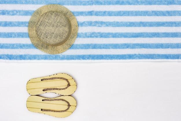 麦わら帽子とコピースペースを持つ白地に黄色のフリップフロップ。ビーチタオルの縞模様。ビーチでの休暇の概念。