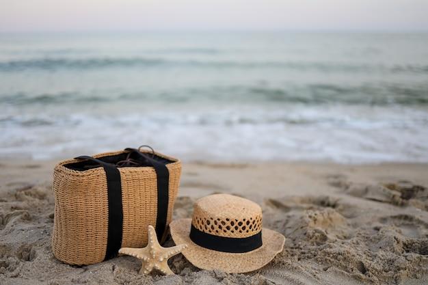 海沿いの美しい砂の上に麦わら帽子、バッグ、ヒトデ