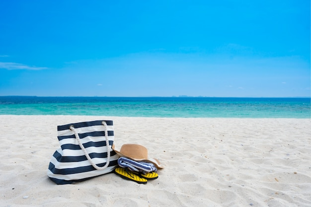 Straw hat, bag,towel and flip flops on a tropical beach