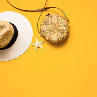 Straw hat, bamboo bag and starfish over yellow background, top view