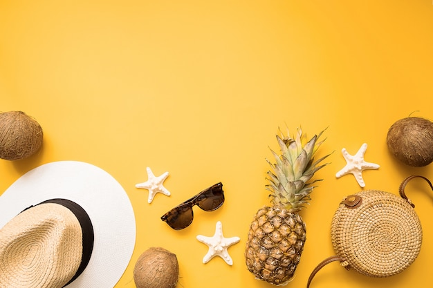 Straw hat, bamboo bag, sunglasses, coconut, pineapple, sea shells and starfish over yellow