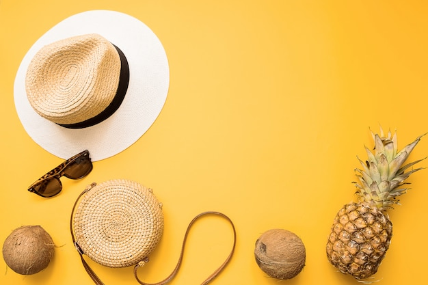 Straw hat, bamboo bag, sunglasses, coconut, pineapple over yellow