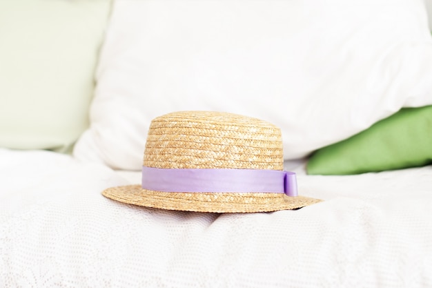 Straw hat on the bed. summer weekend concept. leisure, weekend, trip. woman accessories from above. travel or vacation concept. provence, rustic style. the woman hat on the pillow in bedroom.