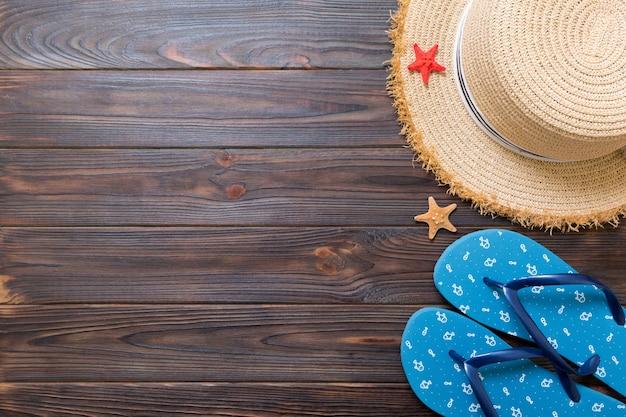 麦わら帽子、青いビーチサンダル、ヒトデ暗い木の背景に。コピースペースと上面図の夏休みのコンセプト。