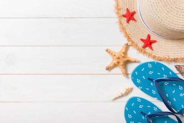 麦わら帽子、青いビーチサンダル、ヒトデ白い木製の背景に。コピースペースと上面図の夏休みのコンセプト。