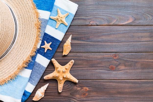 麦わら帽子、青いタオル、ヒトデ白い木製の背景に。コピースペースと上面図の夏休みのコンセプト。