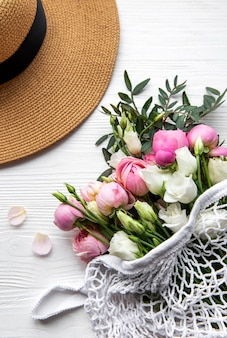 Straw hat and  bouquet of pink rose flowers on white background