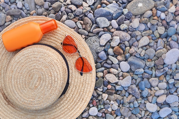 Straw hat, bright orange sunglasses and a bottle of sunscreen for sun protection during sunbathing. copy space