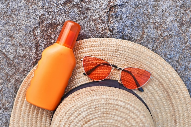 Straw hat, bright red glasses and orange bottle of sunscreen for sun protection