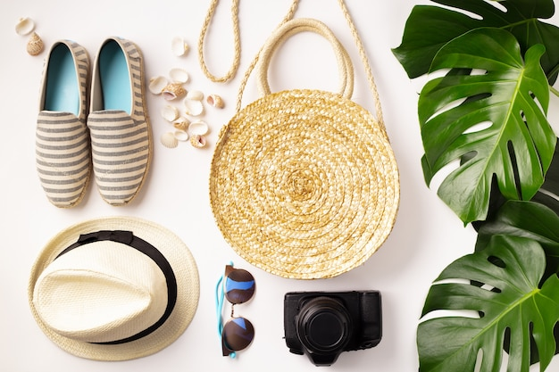 Straw hat, camera, bag, summer shoes, sunglasses, shells and tropical leaves