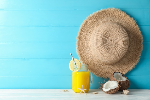Straw hat, coconuts, fresh orange juice and starfishes on white table against color wooden background, space for text. summer vacation concept