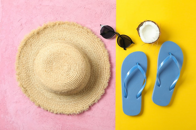 Straw hat, flip flops, sunglasses and coconut on two tone background, space for text and top view. summer vacation concept