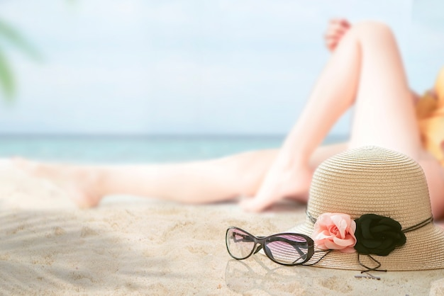 Straw hat and glasses on the beach with blur image of woman in bikini