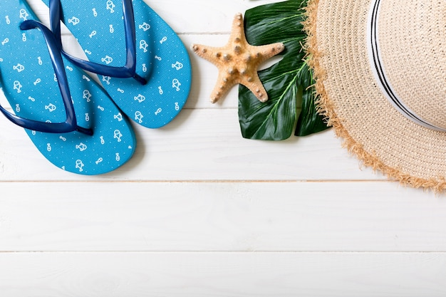 麦わら帽子、緑の葉、青いビーチサンダル、ヒトデ白い木製の背景に。コピースペースと上面図の夏休みのコンセプト。