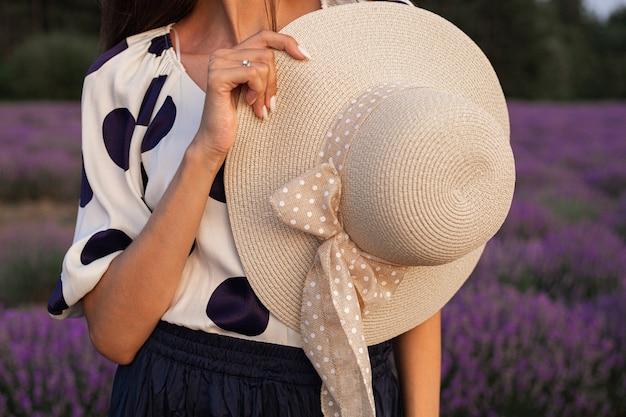 女性の手に麦わら帽子。