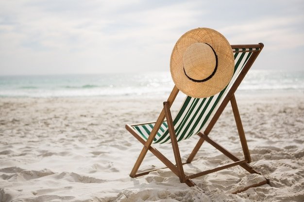 Straw hat kept on empty beach chair