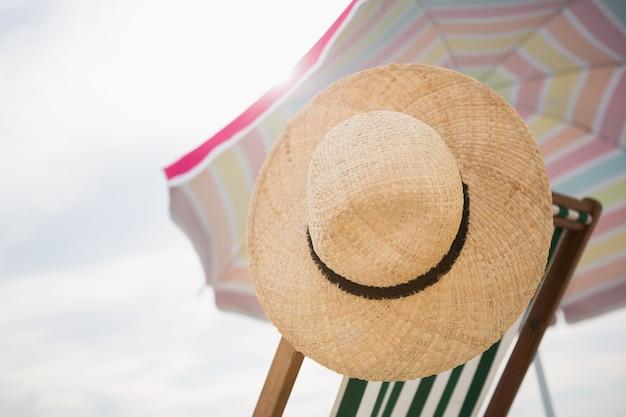 밀짚 모자는 빈 비치 의자에 보관