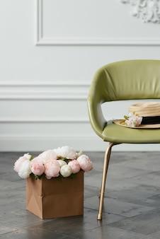 麦わら帽子は、壁の背景に花の花束の横にある緑のアームチェアに横たわっています