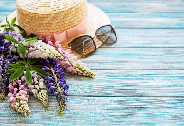 Straw hat and lupine flowers
