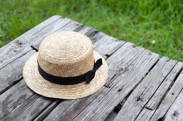 Соломенная шляпа на деревянном столе в саду
