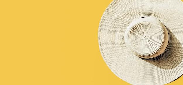 明るい黄色の日当たりの良い背景に麦わら帽子