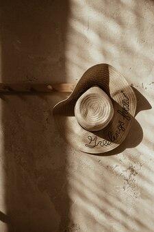 コンクリートの壁にハンガーの麦わら帽子。壁の影。太陽の光の中でシルエット。