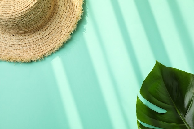Straw hat and palm leaf on mint