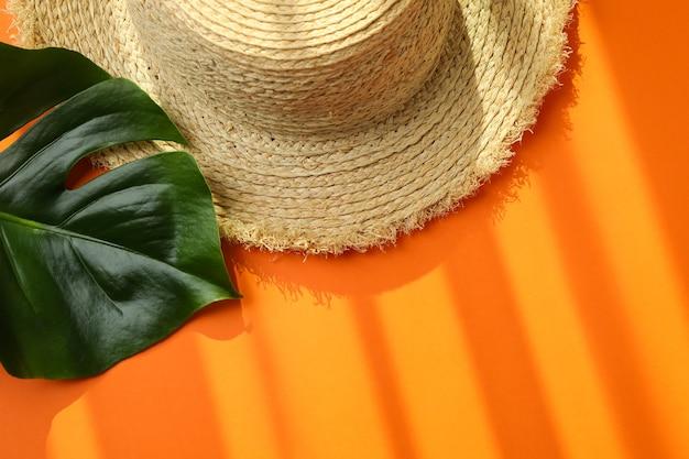 Straw hat and palm leaf on orange isolated background
