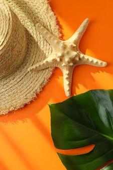 Straw hat, palm leaf and starfish on orange isolated background