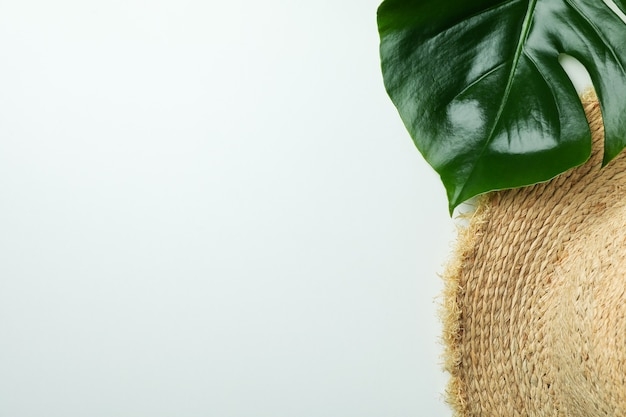 Straw hat and palm leaf on white isolated background