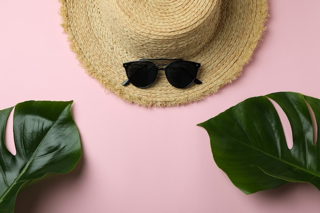 Straw hat, palm leaves and sunglasses on pink isolated background