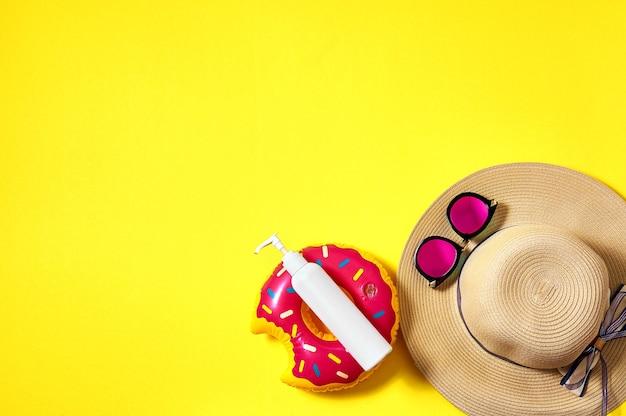麦わら帽子、ピンクのサングラス、日焼け止めボトル、黄色の背景に膨らませてドーナツ。クリエイティブなミニマルコンセプト。上面図フラットレイ