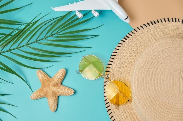 パステルブルーとベージュの表面に麦わら帽子、飛行機、サングラス、ヤシの葉、ヒトデ