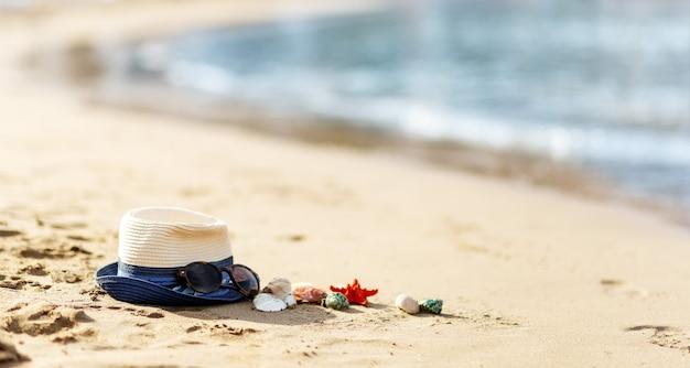 열대 해변의 밀짚모자, 조개, 선글라스