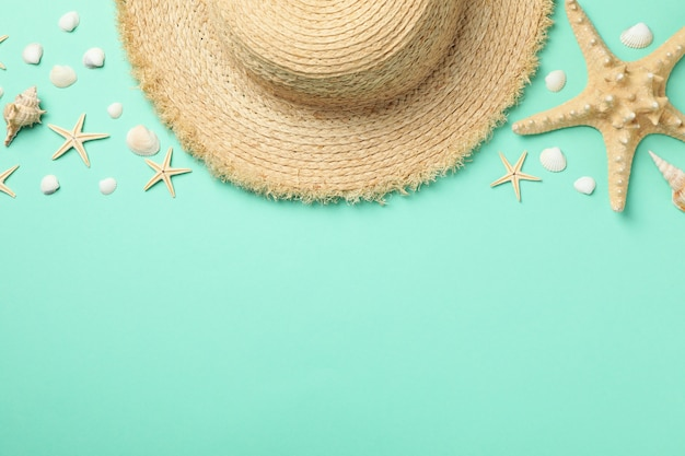 Straw hat and starfishes on green surface