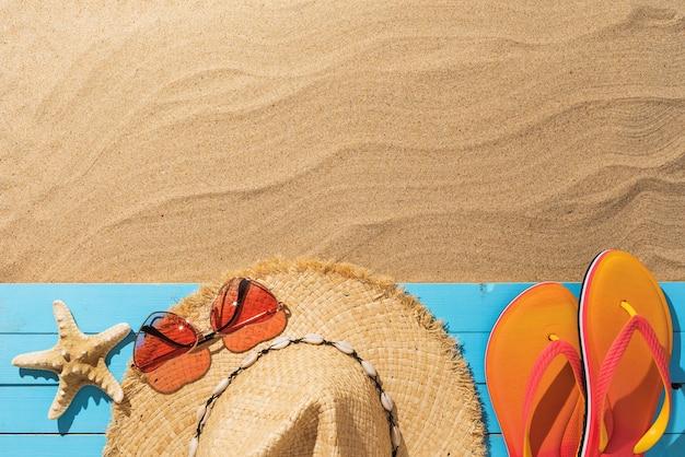 Соломенная шляпа солнцезащитные очки пляжные тапочки и морская звезда на деревянной подставке на песчаном фоне с копией пространства летний фон