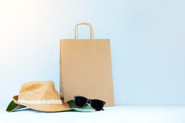 Straw hat sun glasses and brown shopping bag against light blue wall