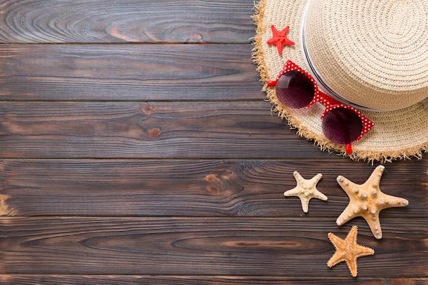 暗い木製の背景に麦わら帽子、サングラス、ヒトデ。コピースペースと上面図の夏休みのコンセプト。